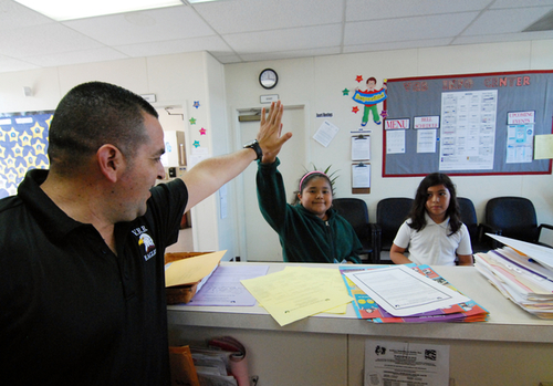 Virginia Rocca Barton Elementary School Principal Jose Juan Urquizo high-fives student Michelle Becerra, who is turning in good behavior points at the front desk.