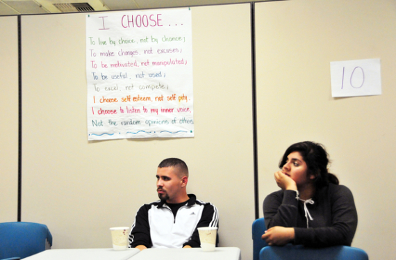 At the Silver Star Resource Center in Salinas, mentors Jose Coronado and Ariana Lopes listen to Leo Jimenez underneath a sign stating the group's pledge.