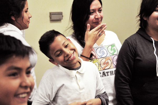"Victor Perez, center, and mentor Anna Camberos smile as the next round of the the ""Titanic"" friendship game is called out at the Silver Star Resource Center in Salinas."