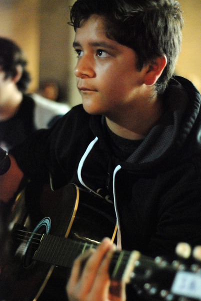 Gustavo Montoro, 13, an advanced student in Felix Miranda's guitar class, waits for his cue at a public performance in front of the CHISPA building during First Friday, a Salinas tradition on Main Street each month.