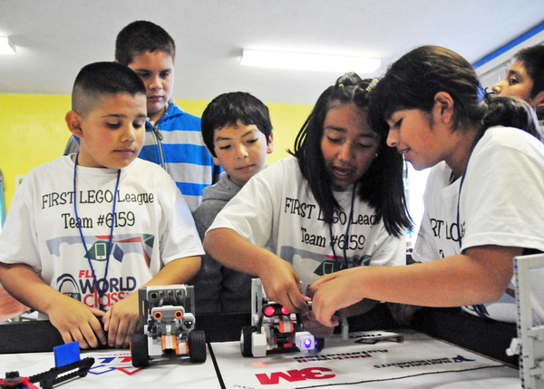 From left, Jonathan Baires, Jose Jimenez, and Brandon Medina watch Dayanara Martinez and Amy Garcia work out a quirk in their robot.