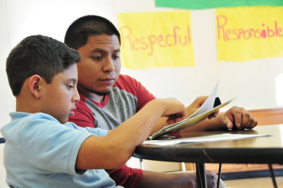 Hartnell College sophomore Stephen Corona, 24, helps Yacer Picazo, a Sherwood Elementary School student, with his English reading.
